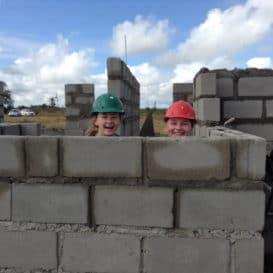 School children behind a breeze block wall