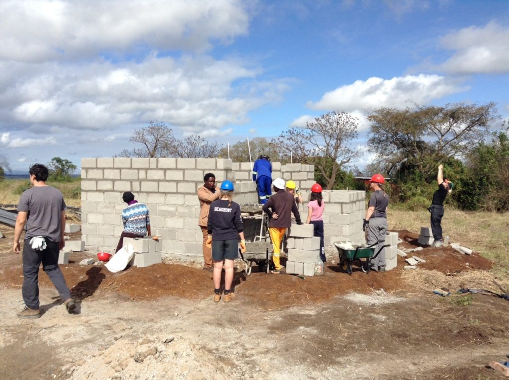 A group of volunteers work together on a building