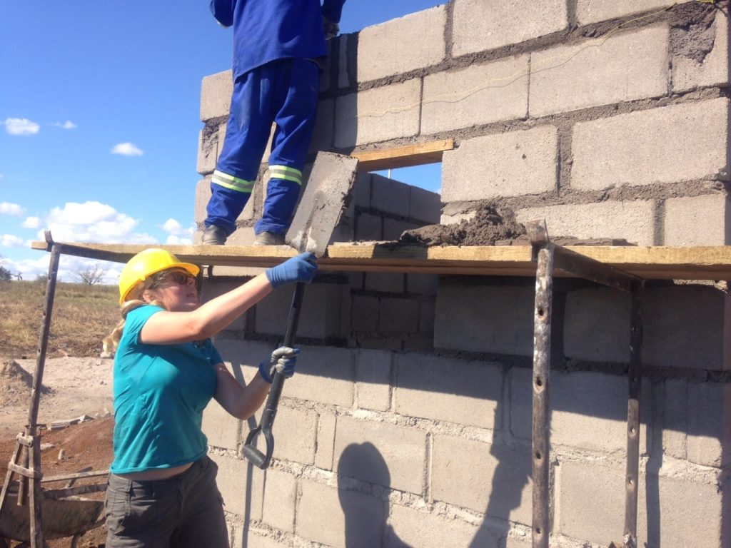Two volunteers working on a wall
